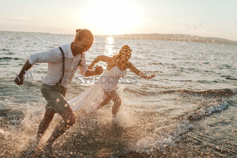 Hochzeitspaar sprintet aus dem Meer