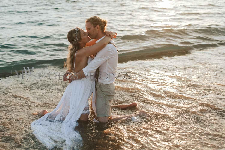 Brautpaar kniet im Wasser